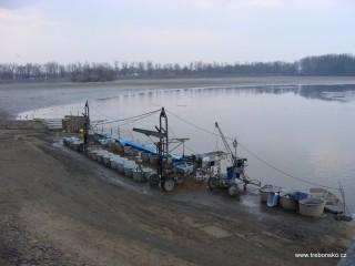 Pohled na kádiště, tj. zpevněné místo u loviště, na němž stojí připravené kádě (nádobí) na vylovené ryby.