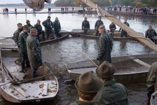 Rybáři s chycenou rybou plují ke kádišti